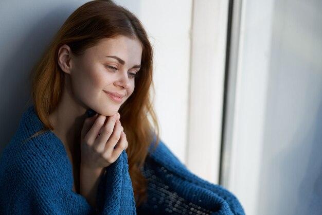 Frau sitzt am fenster mit einem blau karierten morgen