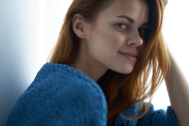 Frau sitzt am fenster mit einem blau karierten verträumten blick. foto in hoher qualität