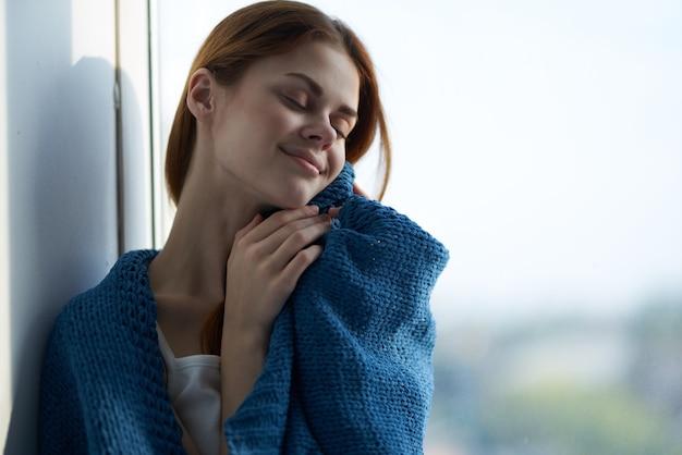 Frau sitzt am fenster mit einem blau karierten verträumten blick