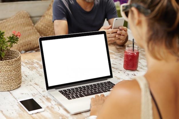 Frau sitzt am hölzernen tisch, der an neuem geschäftsprojekt unter verwendung des laptop-computers arbeitet.