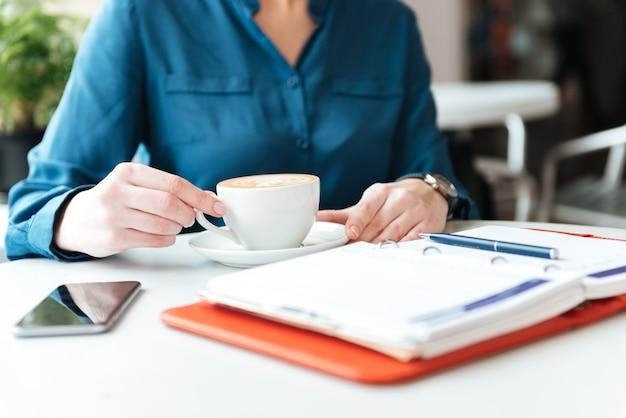 Frau sitzt am kaffeetisch