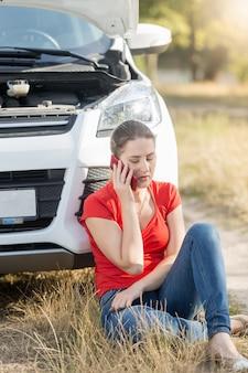 Frau sitzt am kaputten auto und telefoniert