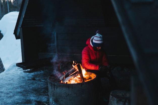 Frau sitzt am lagerfeuer in ihrer blockhütte