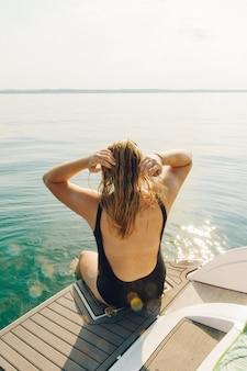 Frau sitzt am rand des bootes und genießt die aussicht, die tagsüber von hinten geschossen wird