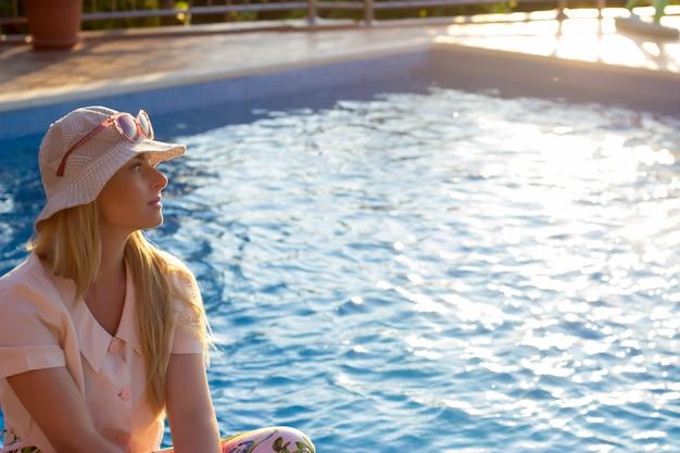Frau sitzt am rand des pools