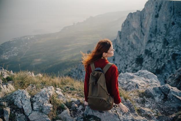 Frau sitzt am rand einer klippe