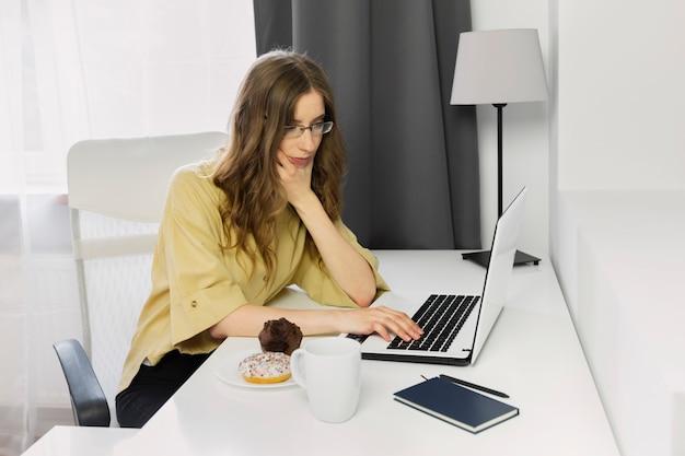 Frau sitzt am schreibtisch mit laptop
