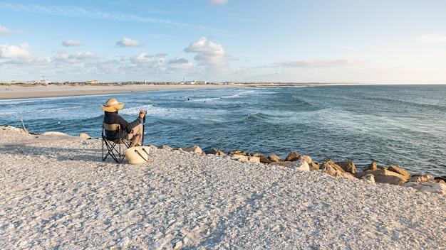 Frau sitzt am strand mit dem rücken zum strand und beobachtet das meer