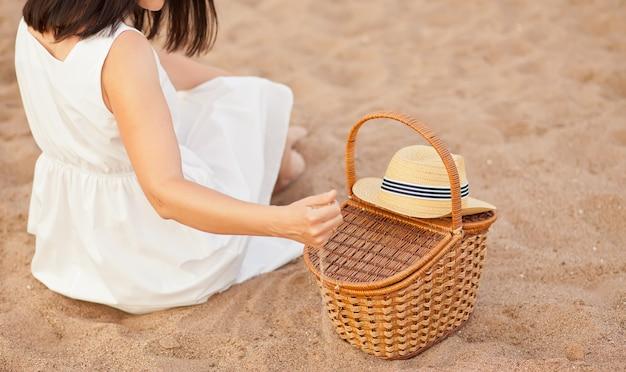 Frau sitzt am strand mit picknickkorb und hut