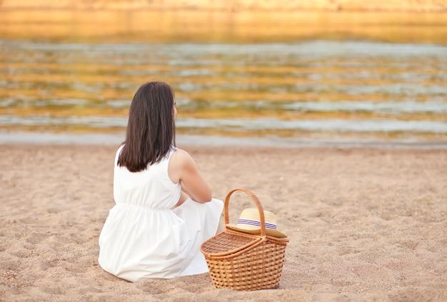 Frau sitzt am strand mit picknickkorb