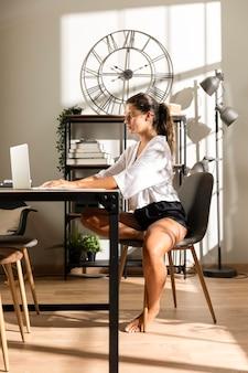 Frau sitzt am tisch und arbeitet am laptop