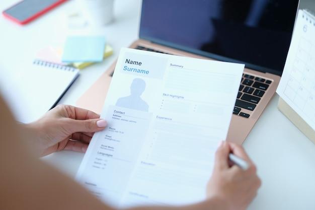 Frau sitzt am tisch vor laptop und hält papier mit lebenslauf für die beschäftigung in den händen