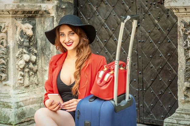 Frau sitzt an der tür mit koffer und smartphone lächelnd
