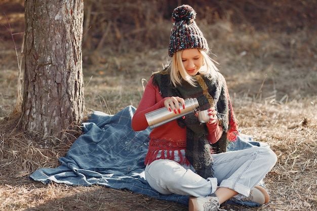 Frau sitzt an einem baum in einem frühlingswald mit einer getränkethermosflasche