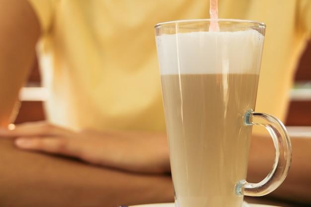 Frau sitzt an einem tisch in einem café und trinkt latte in einem glas mit strohnahaufnahme