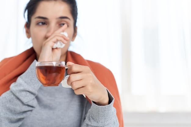 Frau sitzt an einem tisch mit einer decke auf den schultern und behandelt eine erkältung zu hause