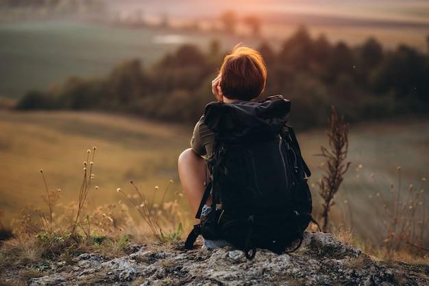 Frau sitzt auf dem berg