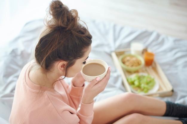 Frau sitzt auf dem bett und trinkt kaffee