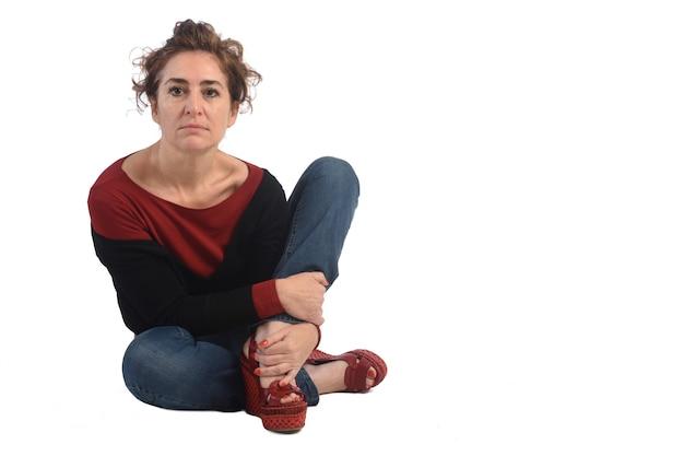 Frau sitzt auf dem boden auf weißem hintergrund