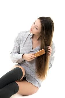 Frau sitzt auf dem boden bürsten ihr haar
