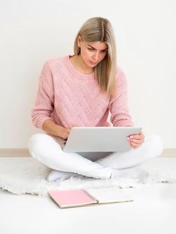 Frau sitzt auf dem boden und besucht einen kurs