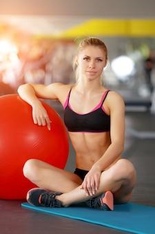 Frau sitzt auf dem boden und lehnte sich gegen einen roten ball