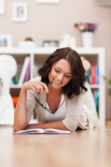 Frau sitzt auf dem boden und liest ein buch