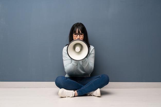 Frau sitzt auf dem boden und schreit durch ein megaphon