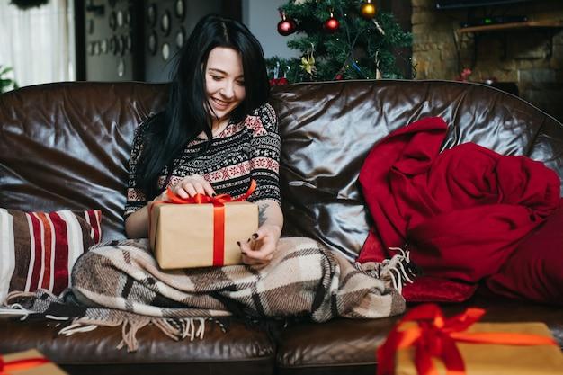 Frau sitzt auf dem sofa mit einer decke und einem geschenk