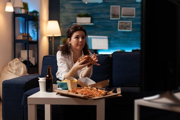 Frau sitzt auf dem sofa und isst leckeren, leckeren burger und schaut sich einen dokumentarfilm an