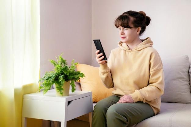 Frau sitzt auf dem sofa und schaut im handy zu hause