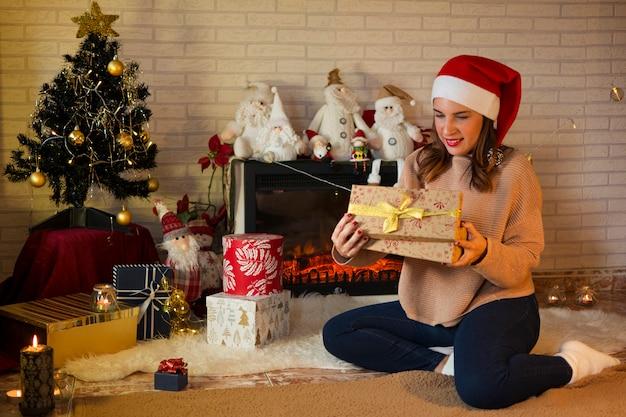 Frau sitzt auf dem teppich, neben dem kamin und öffnet ihre weihnachtsgeschenke