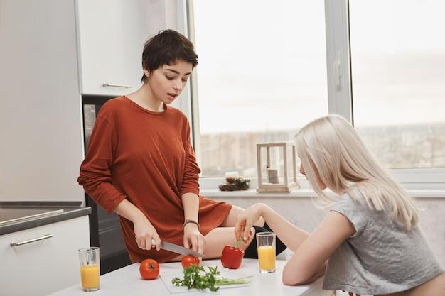 Frau sitzt auf dem tisch, der tomotoes schneidet, während ihr freund orangensaft trinkt