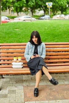 Frau sitzt auf der bank im park mit essen und kaffee zum mitnehmen, mittagspause von der arbeit