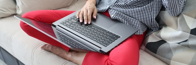 Frau sitzt auf der couch auf ihren füßen liegt laptop