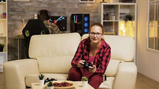 Frau sitzt auf der couch im wohnzimmer und spielt videospiele mit drahtlosen controllern. freund, der spiele auf dem computer im hintergrund spielt.