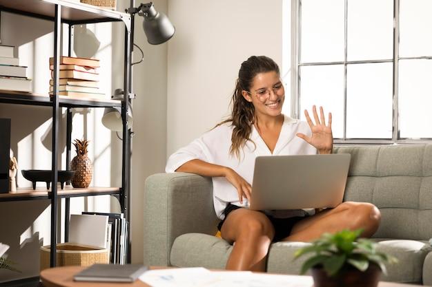 Frau sitzt auf der couch mit laptop