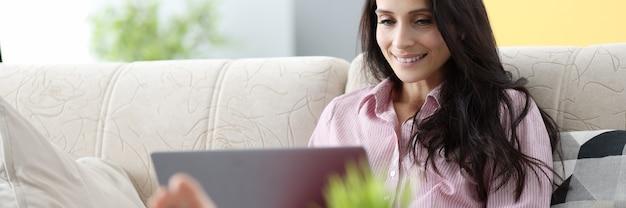 Frau sitzt auf der couch und arbeitet am laptop