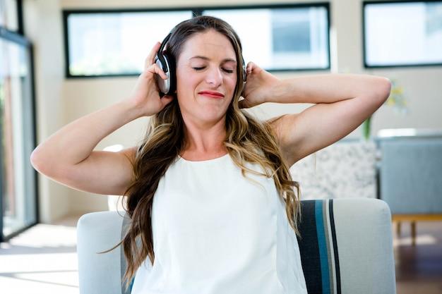 Frau sitzt auf der couch und hört musik über ihre kopfhörer