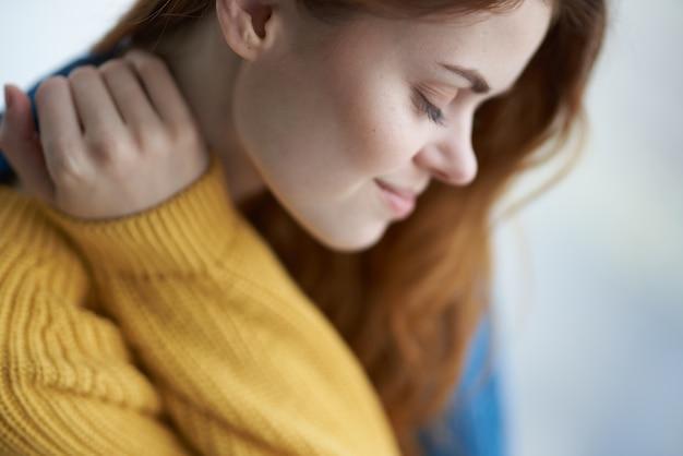 Frau sitzt auf der fensterbank mit einem blau karierten morgen