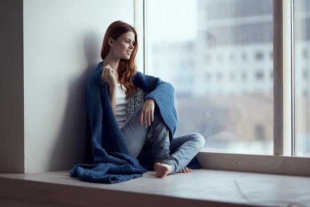 Frau sitzt auf der fensterbank mit einem blau karierten verträumten look
