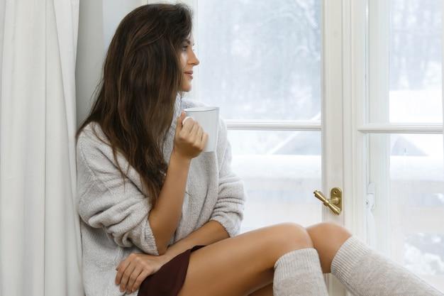 Frau sitzt auf der fensterbank und trinkt heißen tee oder kaffee