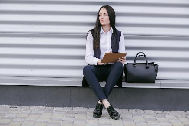 Frau sitzt auf der straße mit einer tablette in den händen