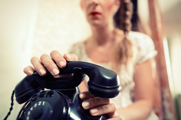Frau sitzt auf der treppe und wartet auf einen anruf