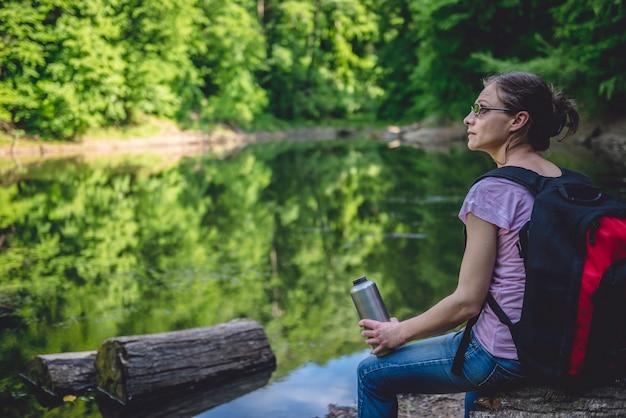 Frau sitzt auf einem baumstamm am see