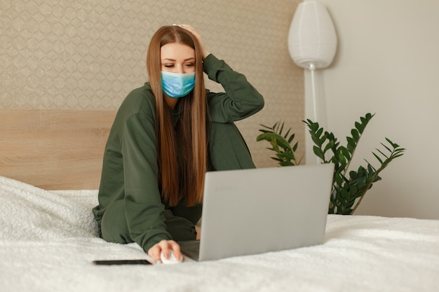 Frau sitzt auf einem bett und benutzt einen laptop
