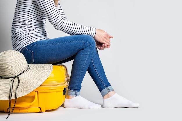 Frau sitzt auf einem gelben plastikkoffer mit einem sommersonnenhut auf einem hellen raum. reisekonzept, flugerwartung, urlaub.