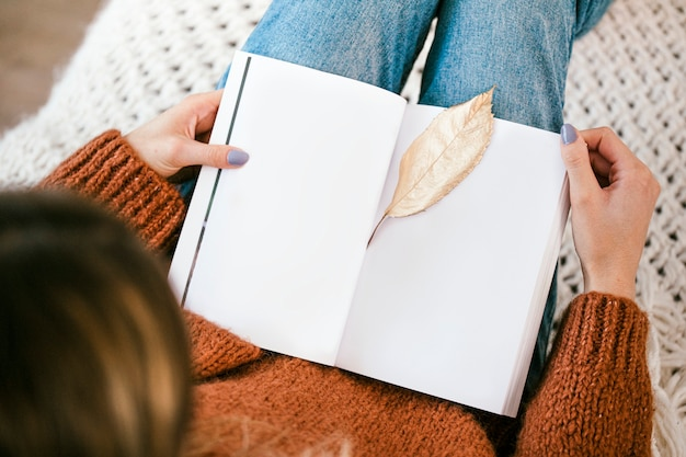 Frau sitzt auf einem gestrickten teppich mit einem goldenen knusprigen blatt auf einem offenen notizbuch