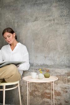 Frau sitzt auf einem hocker und liest ein buch