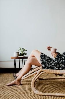 Frau sitzt auf einem korbsitz mit einer tasse tee